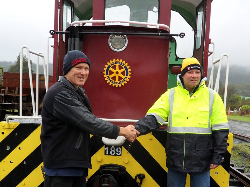 Kevin Joyce, right, and Hugh McCracken, left, celebrate unveiling of Rotary International badge affixed to shunting locomotive Tr 189