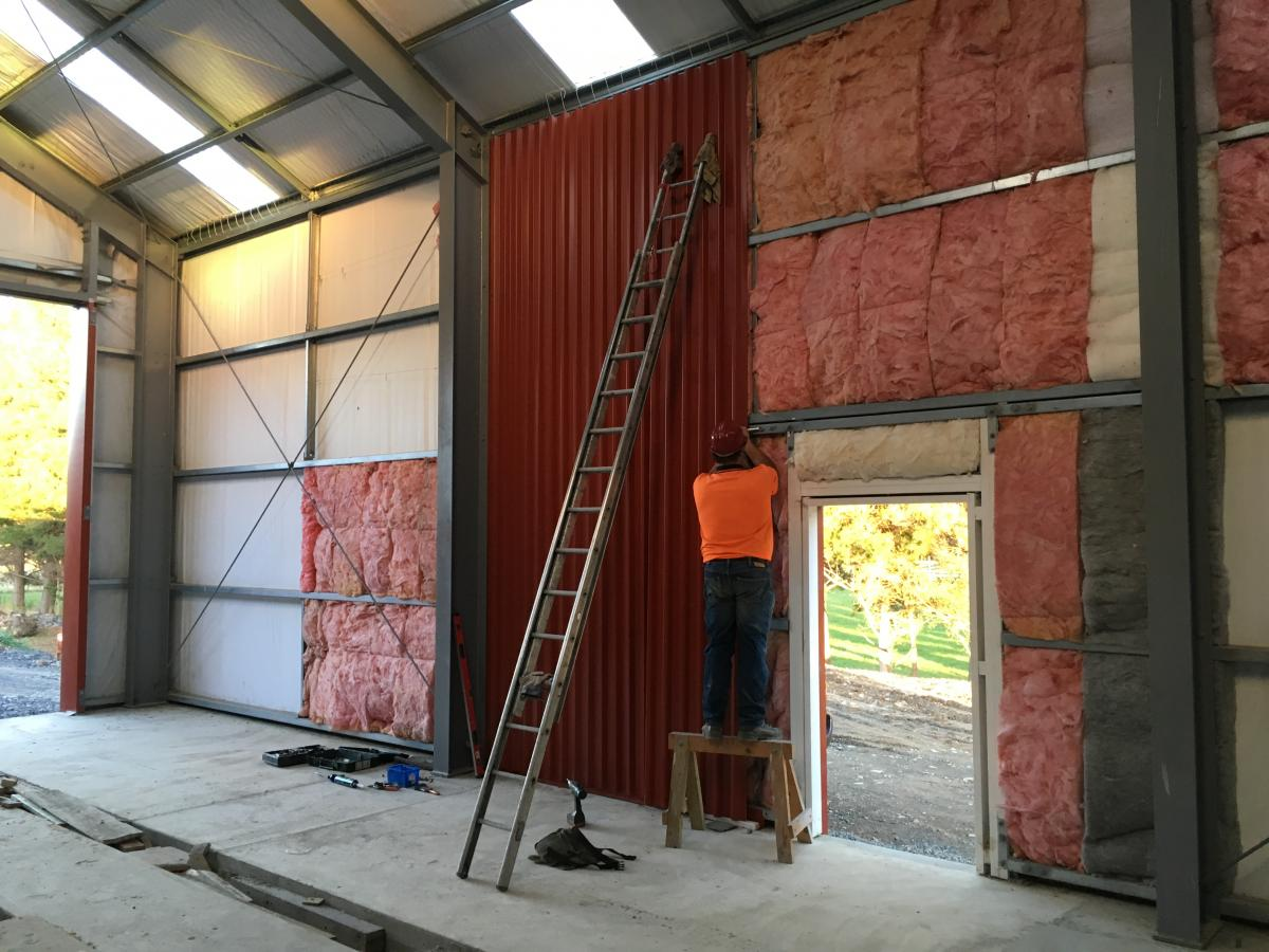 More cladding fitted to internal wall in workshop