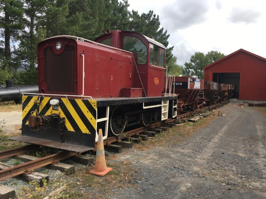 Tr189 shunts Wb 299 frame into the workshop, a rake of ballast wagons used as runners.
